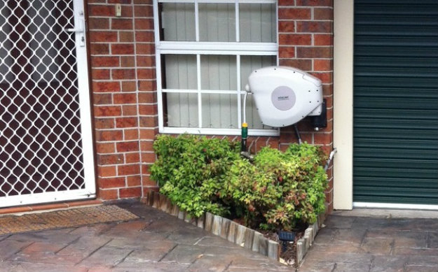 Hoselink Retractable reel mounted at the front of a house by the front door.