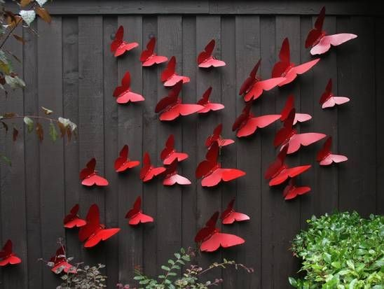 A black fence with 3d red butterflies