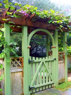 Simple wooden gate painted green with climbing flowers