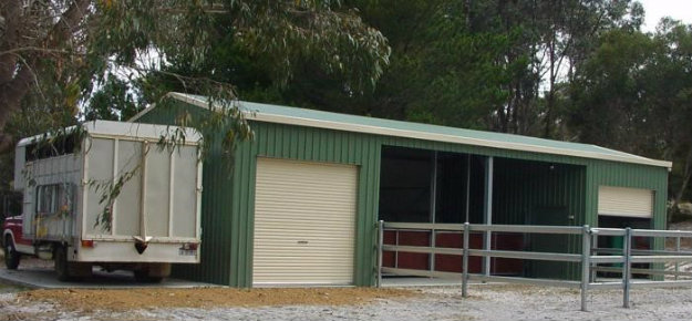 Stables in a yard with a horse van nearby