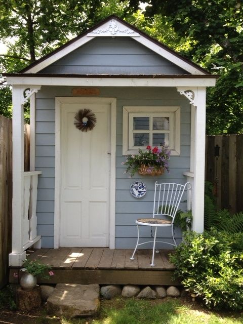 Simple blue shed with verandah and chair
